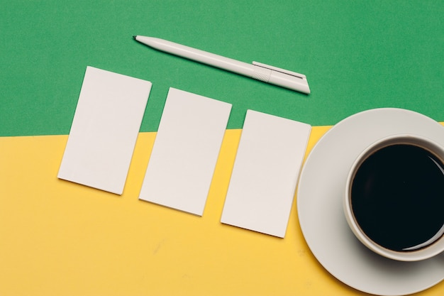 Business cards on a bright background and ballpoint pen coffee cup top view. high quality photo