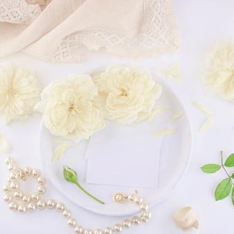Макет визитных карточек на белой тарелке с розами и жемчужным ожерельем.