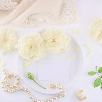 Business cards mockup on a white plate with roses and pearl necklace.