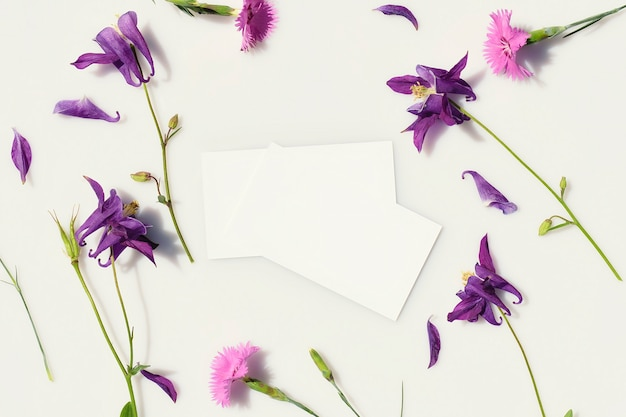 Визитные карточки на сером фоне в окружении свежих голубых и розовых цветов вид сверху
