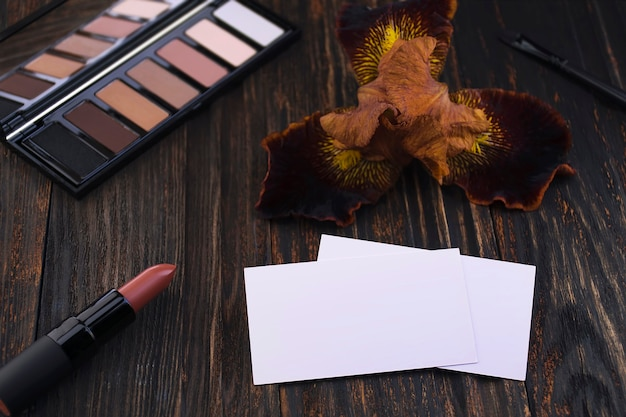 Business cards pink matte nude lipstick and iris flower on a wooden table a brown eyeshadow palette and a brush in the background cosmetics trendy glamorous color mockup