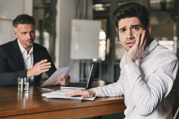 ビジネス、キャリア、配置コンセプト-白人のビジネスマンやディレクターと交渉しながら、オフィスでの就職の面接中に心配して神経質な男を強調