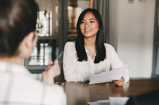 Business, career and placement concept - joyful asian woman smiling and holding resume, while sitting in front of directors during corporate meeting or job interview