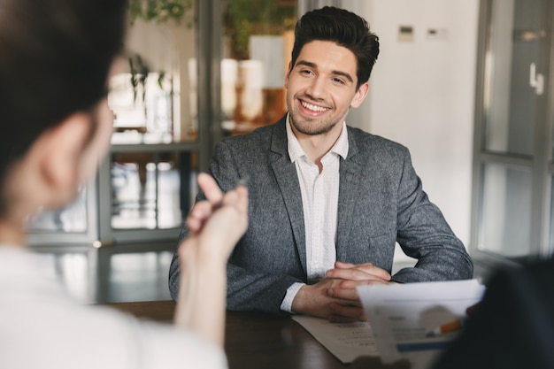 Business, career and placement concept - smiling caucasian man 30s negotiating with committee of businesslike people, during job interview in office