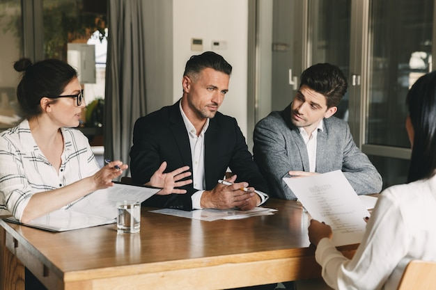 Business, career and placement concept - three executive directors or head managers sitting at table in office, and discussing work with new personnel during interview