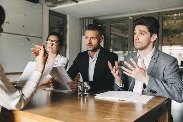Business, career and placement concept - three executive directors or head managers sitting at table in office, and negotiating with new personnel during interview