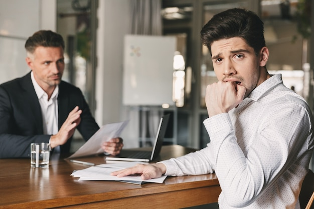 Business, career and placement concept - uptight nervous man worrying during job interview in office, while negotiating with caucasian businessman or director
