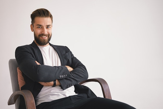 Concetto di affari, carriera e successo. allegro ed elegante giovane uomo d'affari con la barba lunga con un sorriso felice, seduto in poltrona contro il muro bianco con copia spazio per le vostre informazioni