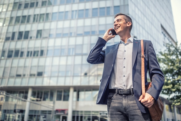 Business casual dress for man who talks on a cell phone in front of the office building smiling.