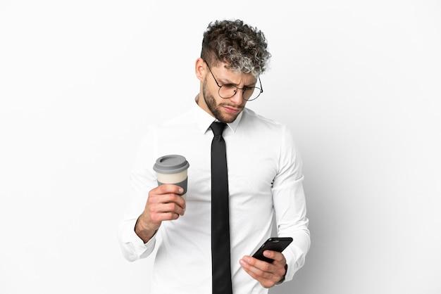 持ち帰り用のコーヒーと携帯電話を保持している白い背景で隔離のビジネス白人男性