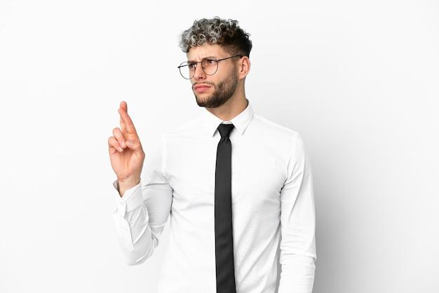 Деловой человек кавказской изолирован на белом фоне со скрещенными пальцами и желает лучшего