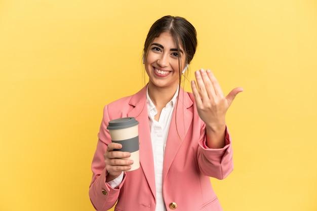 노란색 배경에 격리된 비즈니스 백인 여성이 손을 잡고 초대합니다. 당신이 와서 행복