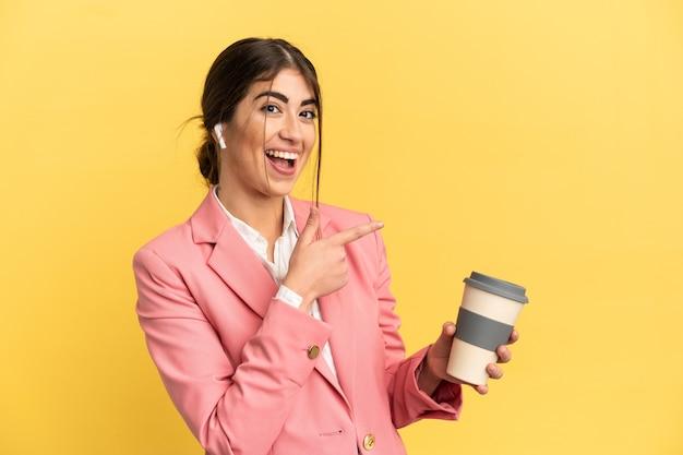 노란색 배경에 격리된 비즈니스 백인 여성이 손가락을 옆으로 가리키고 제품을 제시합니다.