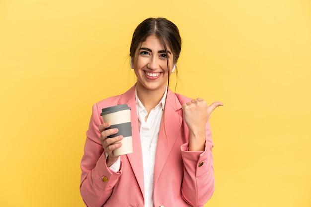 제품을 제시하기 위해 측면을 가리키는 노란색 배경에 고립 된 비즈니스 백인 여성
