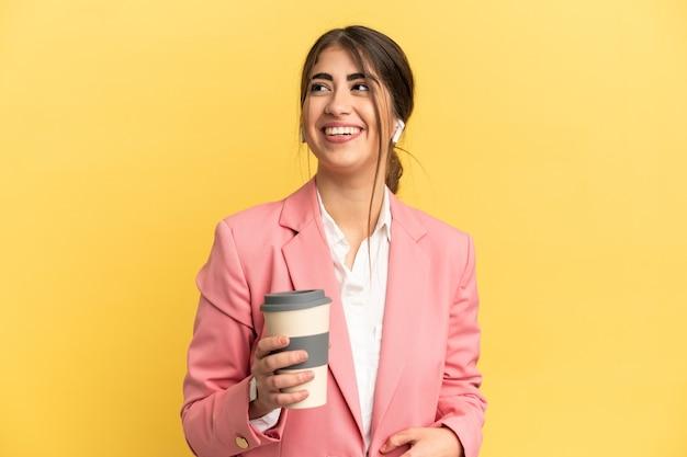 Деловая женщина кавказской изолирована на желтом фоне позирует с руками на бедрах и улыбается