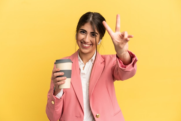 笑顔と勝利の兆候を示す黄色の背景に分離されたビジネス白人女性