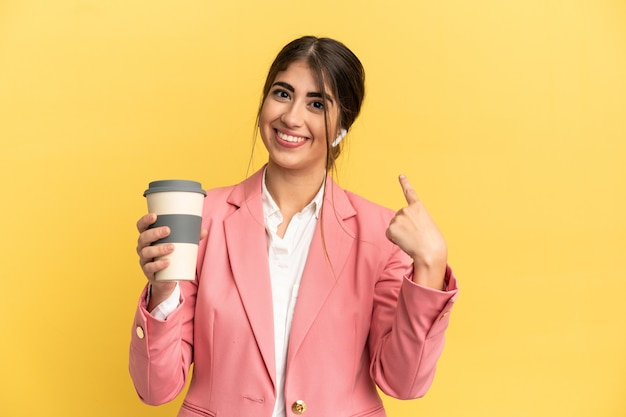 Business caucasian woman isolated on yellow background giving a thumbs up gesture