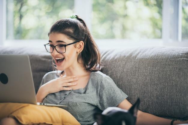 ラップトップコンピューターを使用して自宅でオンラインビジネスを行うビジネス白人女性、通信技術の観点からノートブックで作業する屋内ライフスタイルに座っている若い女性