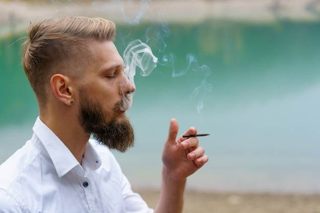 Business caucasian young bearded man in a white shirt smokes a cigarette and blows smoke against the...