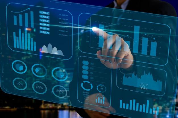 ビジネスチャートとグラフ。仮想画面ホログラムに触れるビジネスマン。ビジネス技術の概念