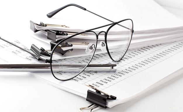 Бизнес-диаграмма, лист бумаги и очки на белой поверхности