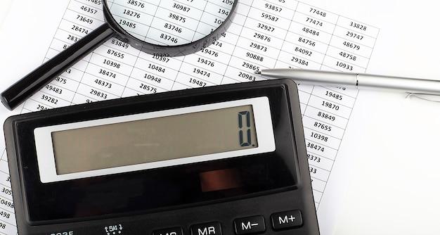 経済的な成功を示すビジネスチャート、電卓とペン、ビジネス
