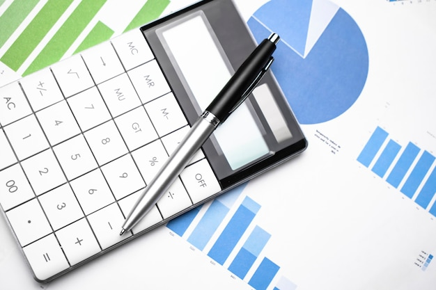 Business chart showing financial success at the stock market with pen and calculator