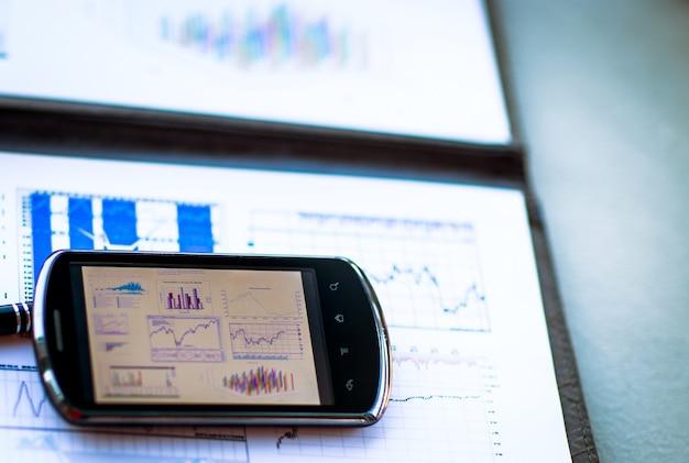 Бизнес-диаграмма со смартфоном и ручкой на столе