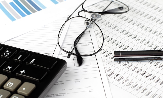 Business chart with pen, calculator and glasses close up