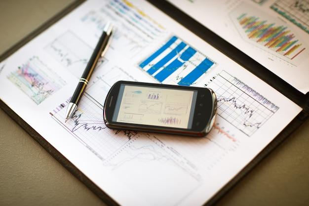 Бизнес-диаграмма со смартфоном и ручкой
