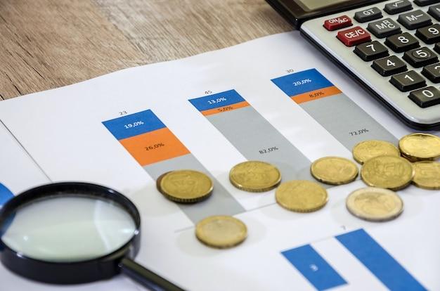 사무실 세무 회계 통계 및 분석의 나무 탁자에 있는 비즈니스 차트와 돈
