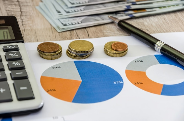 統計と分析のオフィス税会計の木製テーブルのビジネスチャートとお金