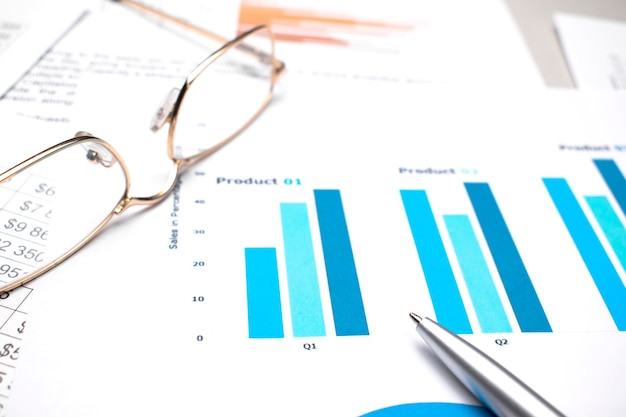 Business charts black and blue with calculator, glasses and pen