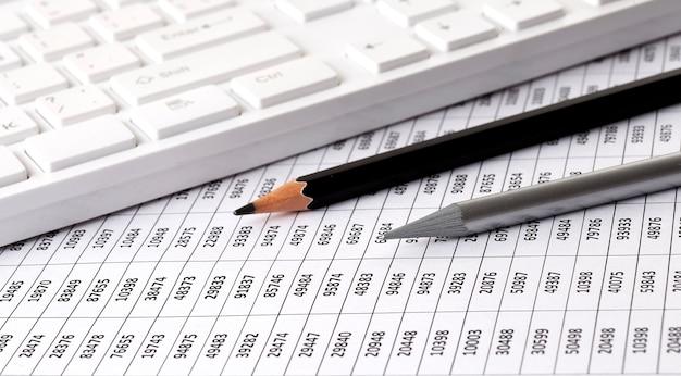 Отчет о бизнес-диаграммах с клавиатурой на столе финансового консультанта. финансовые концепции.