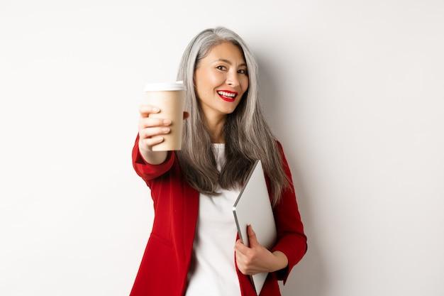 사업. 쾌활 한 아시아 여자 관리자 커피 한 잔을주고 웃 고, 노트북을 손에 서, 흰색 배경.