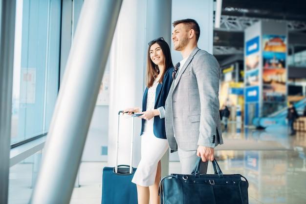 空港で荷物を持つビジネスクラスの乗客、背面図。ビジネスマンやエアターミナルのビジネスウーマン