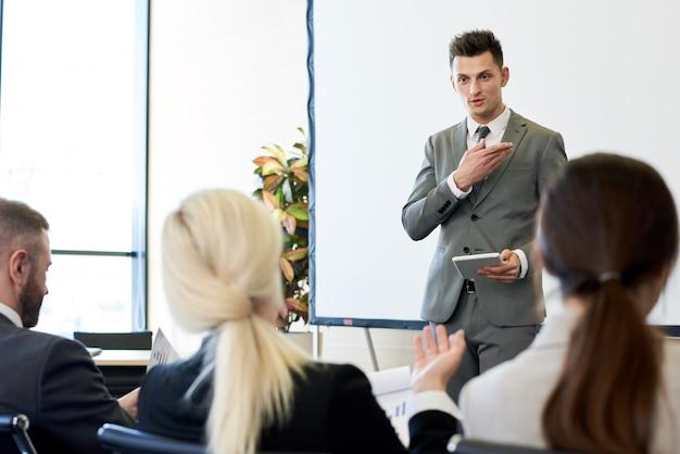 フォーラムでスピーチを与えるビジネスコーチ