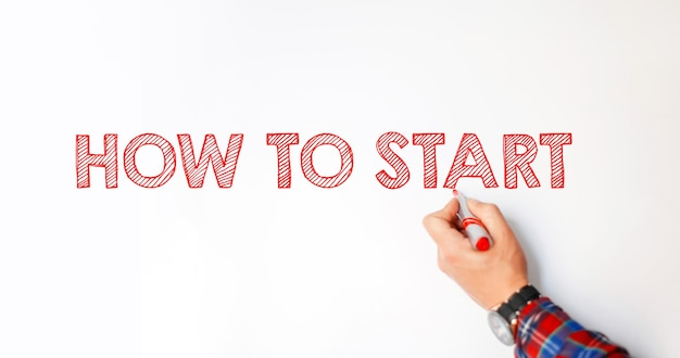 ビジネスコーチの男性は、ホワイトボードに次のテキストを書き込みます。開始方法。創造的なアイデアとモチベーション