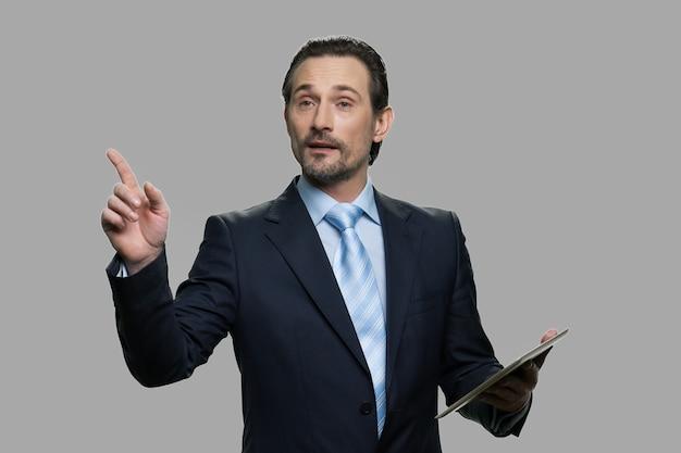 デジタルタブレットを使用するビジネスコーチ。灰色の背景で成功したビジネススピーカー。ビジネスマンは、新しいビジネス戦略を説明します。