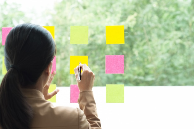Business colleague using notes on glass wall