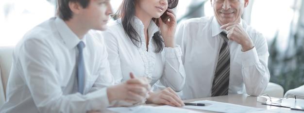 オフィスのデスクに座って財務統計を分析している同僚。