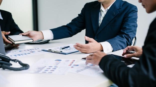 同僚はオフィスで共同で財務情報について話し合っています。