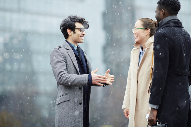 Business colleagues chatting in snowy street