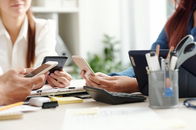 Business colleagues communication via messengers or checking social media on smartphones when having short meeting break