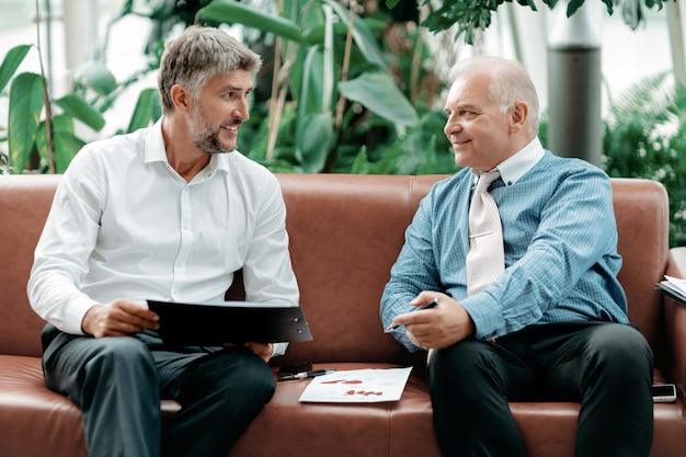 Деловые коллеги обсуждают финансовые документы перед старти