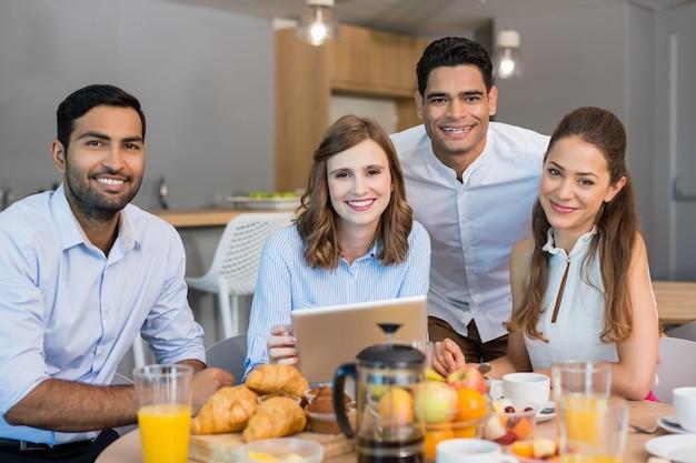 사무실 카페테리아에서 아침 식사를하면서 디지털 태블릿을 통해 논의하는 비즈니스 동료