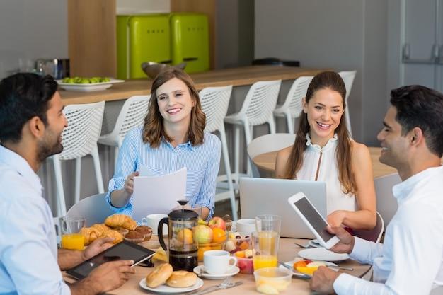 아침 식사를하면서 디지털 태블릿을 통해 논의하는 비즈니스 동료