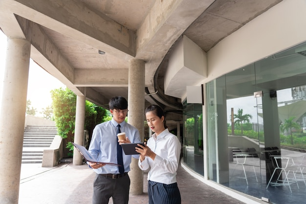 Business colleagues discussing work issues outdoor near the office building, talking to each other outdoors.