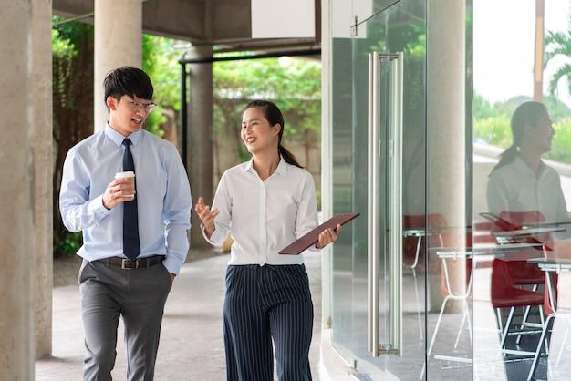 オフィスビルの近くで屋外で仕事の問題について話し合っている同僚が、屋外で互いに話し合っています。