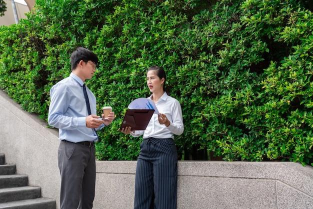 사무실 건물 근처 야외 작업 문제를 논의하는 비즈니스 동료, 야외에서 서로 이야기.